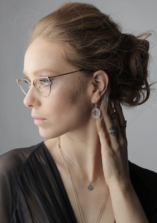 黑色v領襯衫的女人穿著銀色鏡框的眼鏡