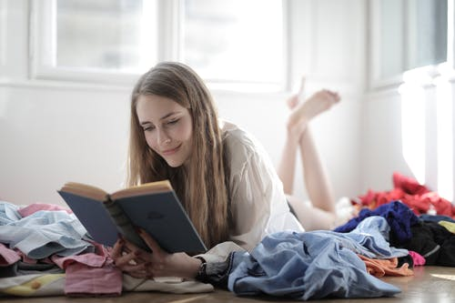 Woman Lying Down While Reading a Book