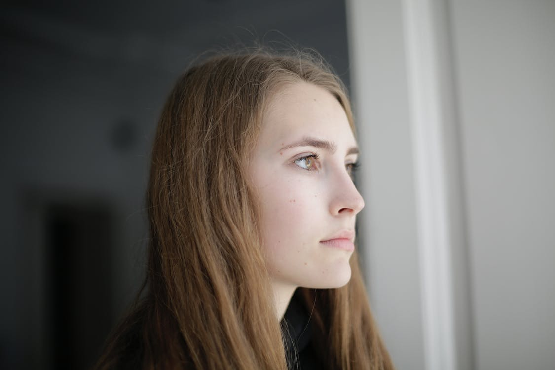 Pensive young woman in living room
