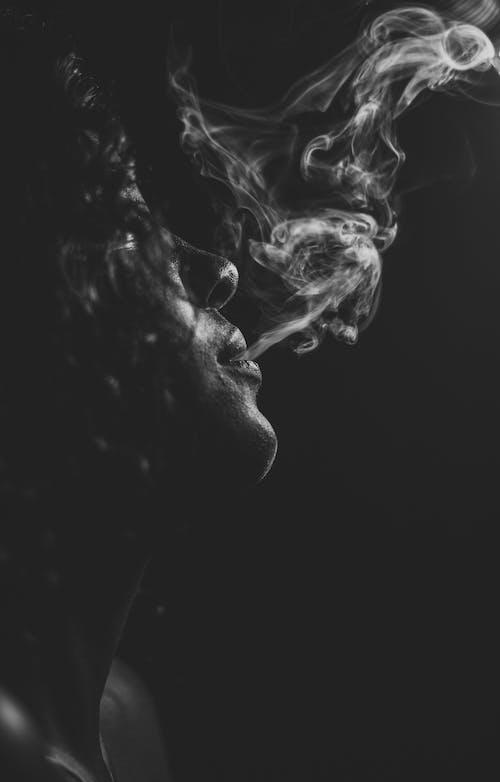 Grayscale Photo of Woman Smoking