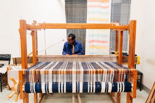 Ethnic craftsman working on loom in workshop