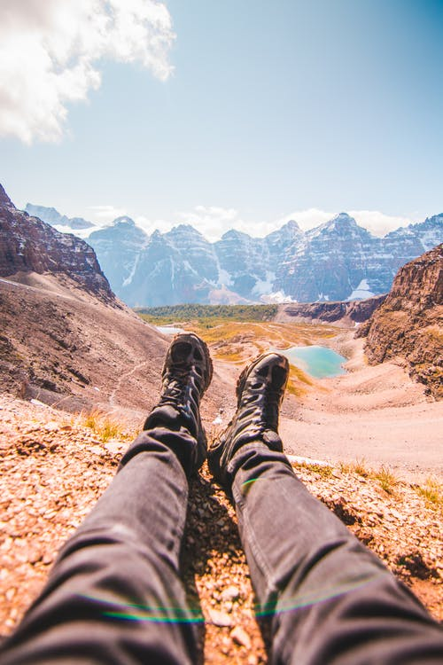 Person in Black Pants and Black Hiking Shoes Sitting on Brown Rock Mountain