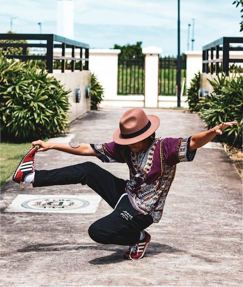 Unrecognizable ethnic dancer showing original trick on pavement near bushes
