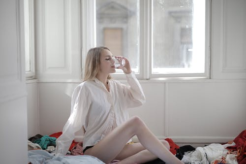 Woman in White Long Sleeve Shirt While Drinking Water