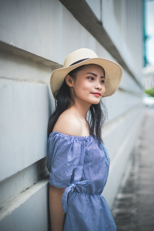 Woman in Blue Off Shoulder Dress Wearing Brown Hat