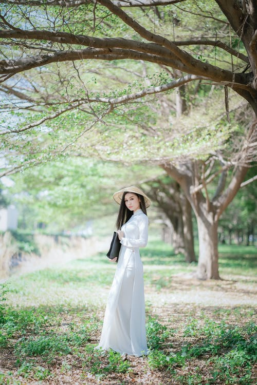 Woman in White Long Sleeve Dress Standing Under Brown Tree