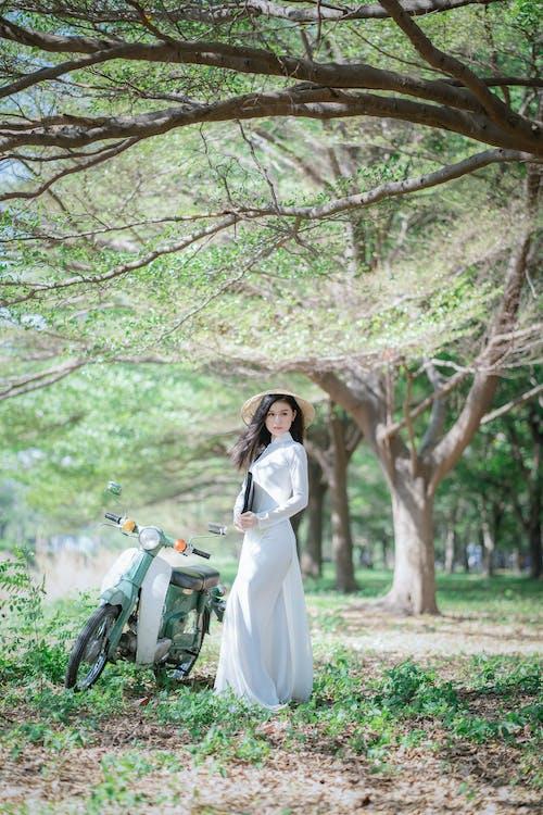 Woman in White Long Sleeve Dress Standing Beside Motorcycle