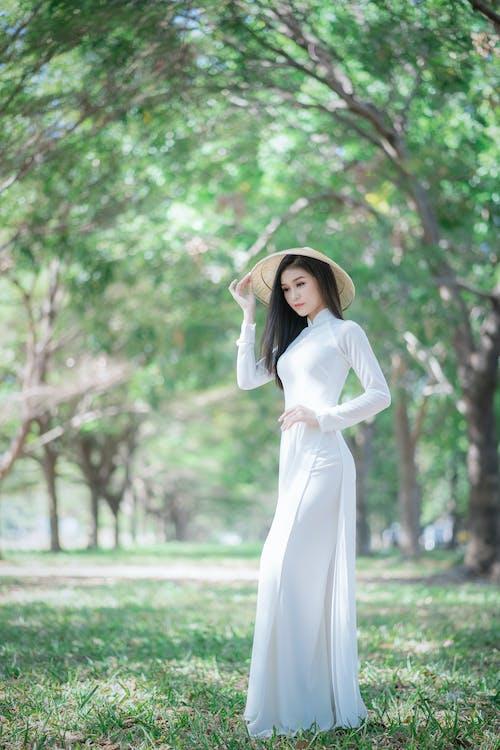 Woman in White Long Sleeve Dress Standing on Green Grass Field