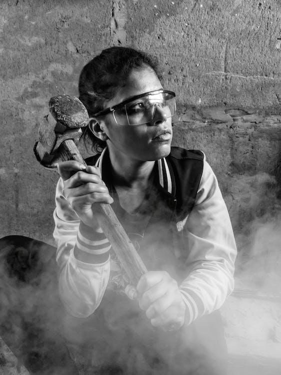 Monochrome Photo of Woman Holding Hammer