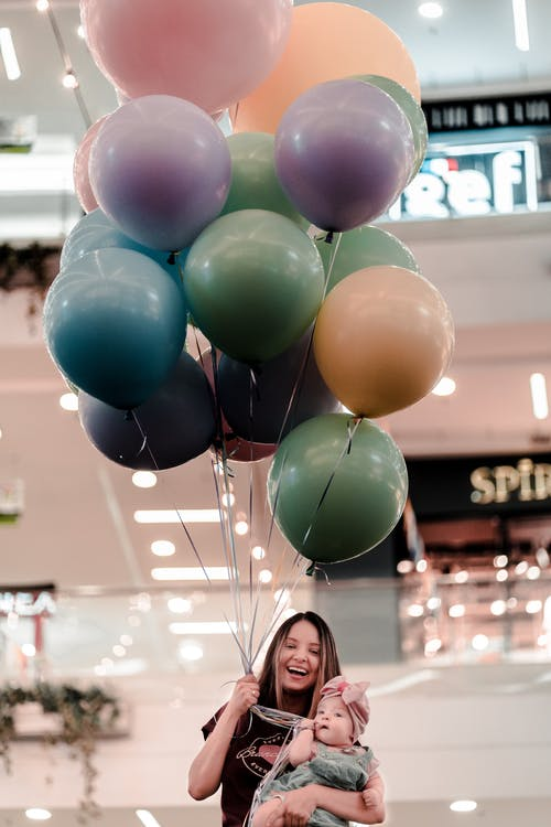 Woman Holding Colorful Balloons and Her Baby