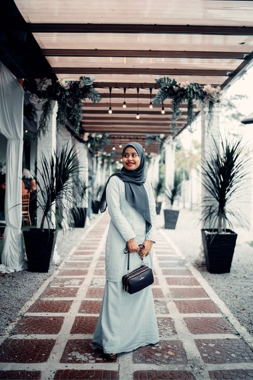 Woman in Gray Hijab Standing on Sidewalk