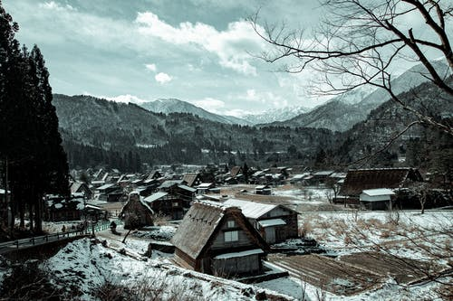 Village with houses near mountains in winter under cloudy sky