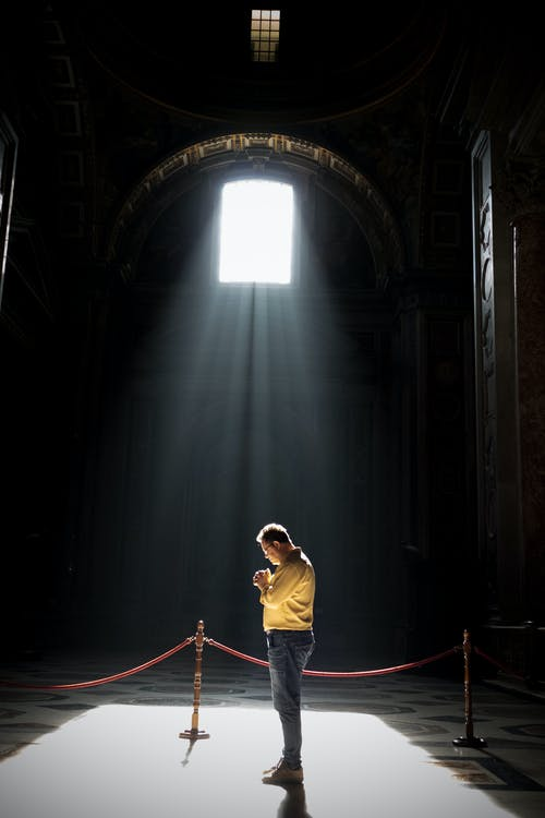 Unrecognizable man praying in church in sunlight