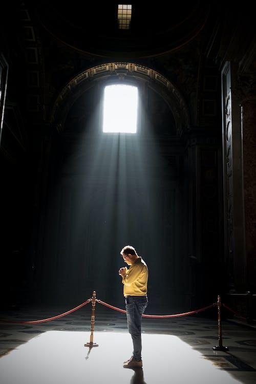 Unrecognizable man praying in church in sunlight