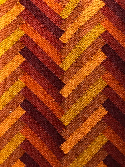 Closeup of textured background of bright fabric made of natural material representing symmetrical lines with different red and brown color shades