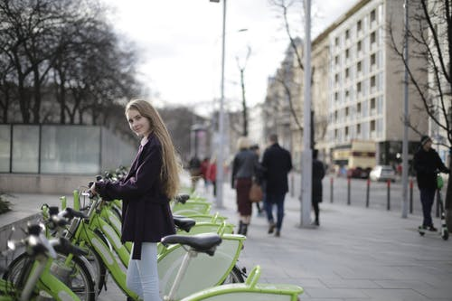 Woman in Violet Coat Standing by Green Bicycles