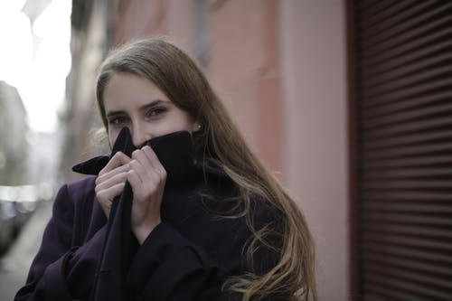 Woman Wearing Violet Coat While Covering Her Face With Her Hands