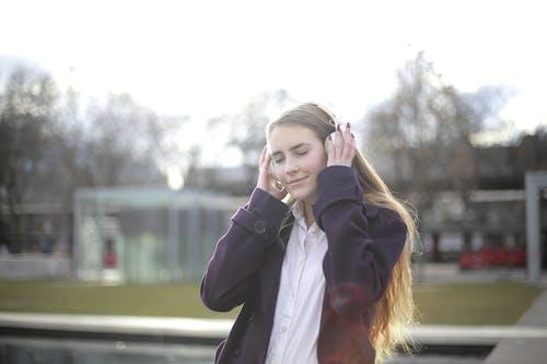 白いヘッドフォンを保持している紫のコートの女性