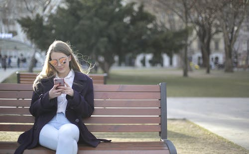Woman Using Cellphone While Sitting on Wooden Bench