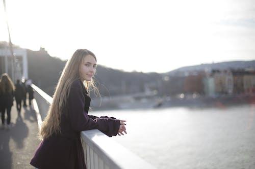 Femme Portant Un Manteau Violet Tout En S'appuyant Sur Une Balustrade En Métal