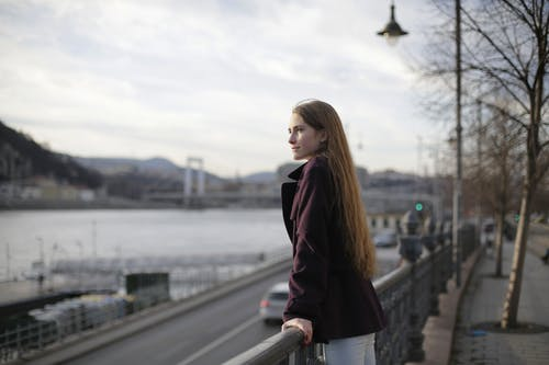 Woman in Violet Coat Standing Near Metal Railing