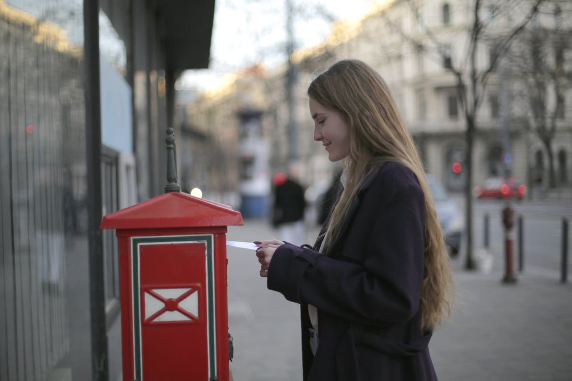 Woman in Black Coat Standing Beside Red Telephone Booth