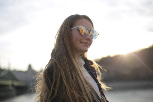 Woman in Purple Jacket Wearing Silver Framed Aviator Sunglasses