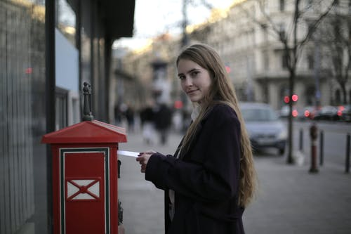 Woman Wearing Violet Coat While Standing Near Mailbox