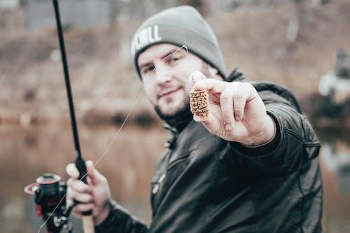 Man in Black Jacket Holding Fishing Bait