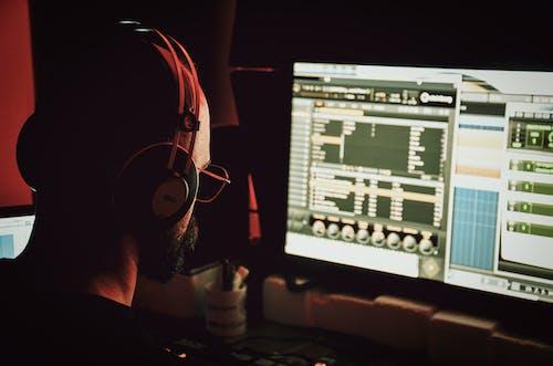 Unrecognizable male DJ in headset working on desktop computer