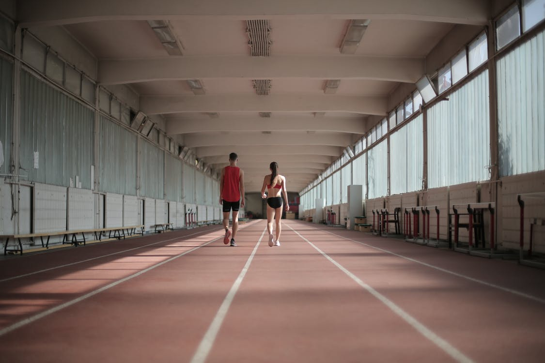 Back view of sportsman and sportswoman in activewear walking along running track in athletics arena during warming up before training