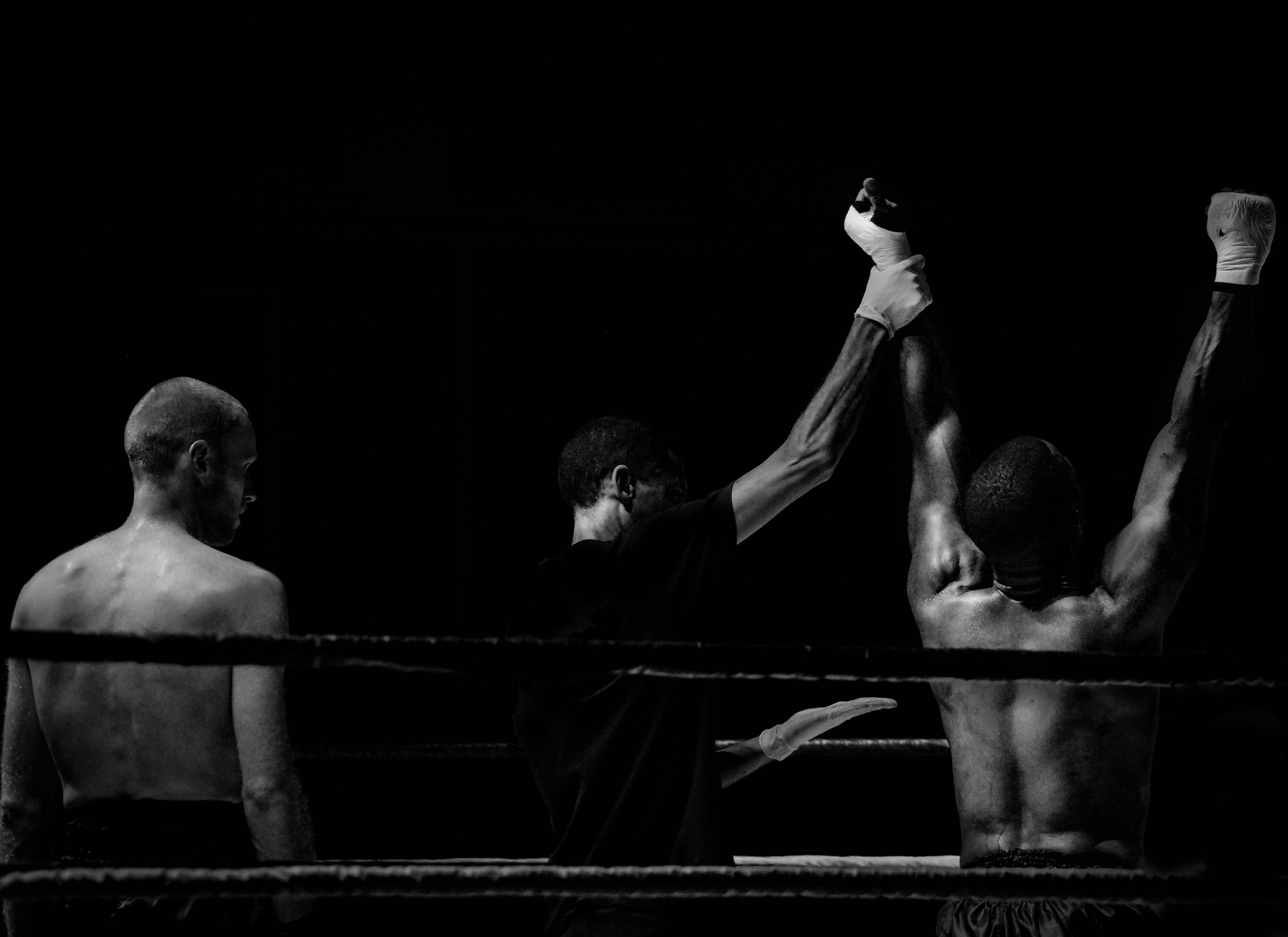 Grayscale Photography of Man Holding Boxer's Hand Inside Battle Ring