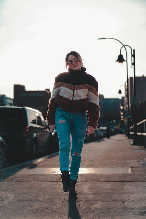 Woman in Blue Denim Jeans Walking on Sidewalk