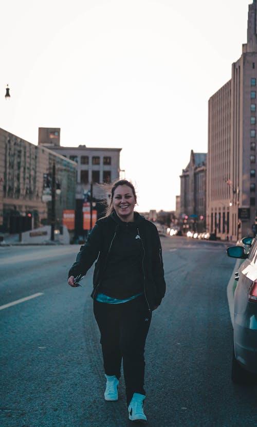 Woman in Black Jacket Walking on Road