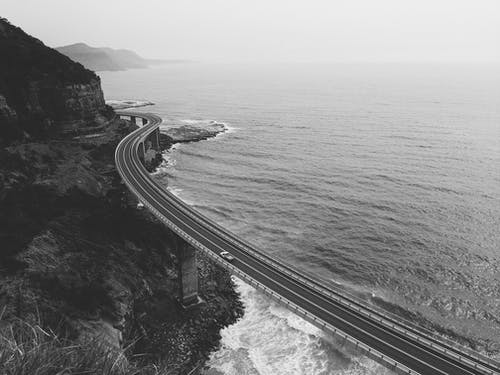 Grayscale Photo of Road Near Body of Water