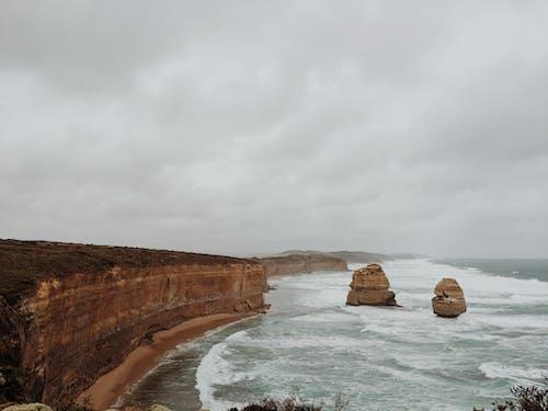 Brown Rock Formation on Sea Under Grey Sky