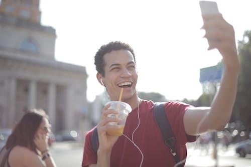 T Shirt Pria Berleher Kru Merah Memegang Gelas Plastik Bening Saat Mengambil Foto Selfie