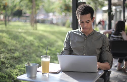 Focused black male freelancer using laptop in street cafe
