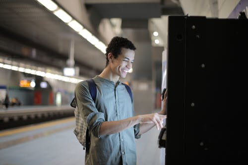 Joyful young African American male in casual clothes with backpack focusing and interacting with vending machine at underground station against blurred railway platform