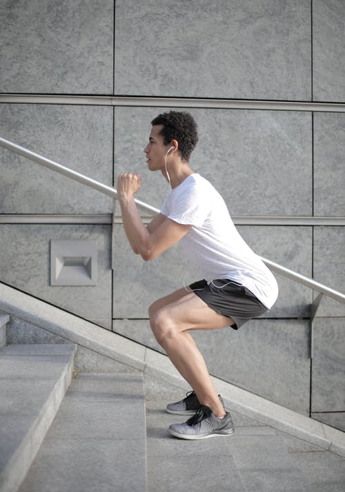 Young ethnic focused sportsman exercising on stairs in city