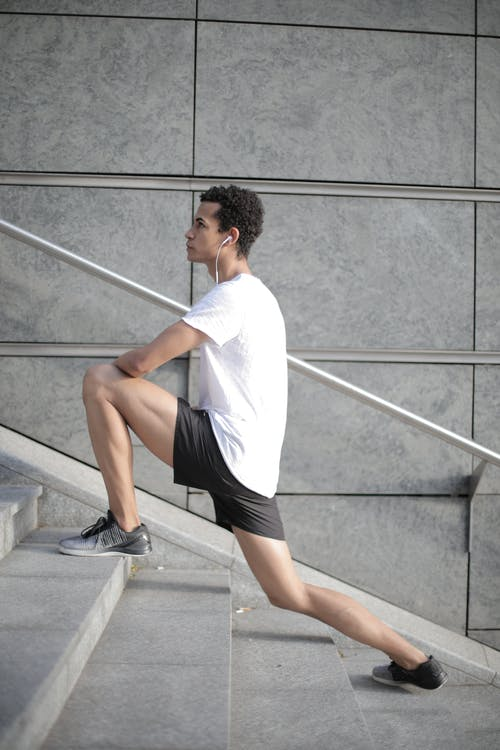 Millennial ethnic male athlete stretching legs on stairs in city