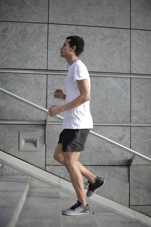 Muscular determined ethnic male athlete is running up stairs on street