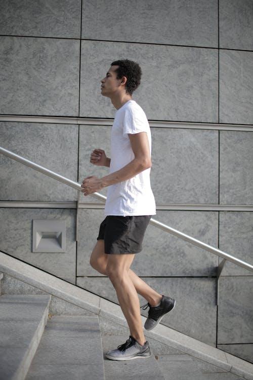 肌肉確定族裔男性運動員在大街上跑上樓梯