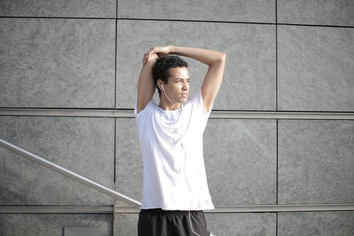 Calm pensive African American sportsman in earphones and sportswear looking away and thinking while stretching arms and listening to music with pleasure on street against gray exterior of contemporary buildings