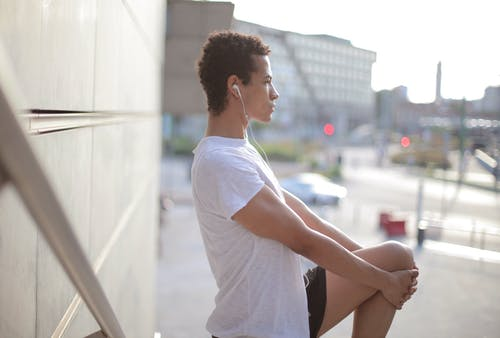 Side view of calm thoughtful African American male athlete in earphones and sportswear looking away and stretching leg while standing alone and listening to music on street near modern building in city