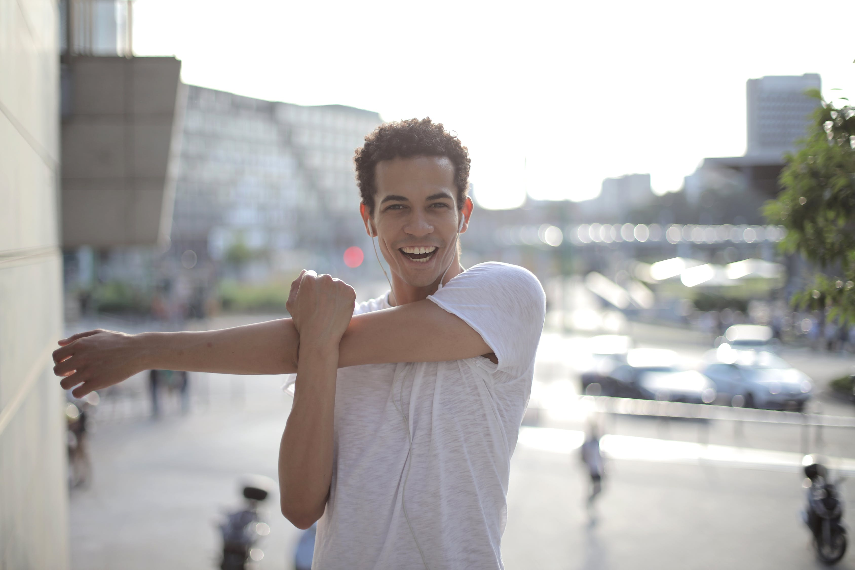 Cheerful African American male athlete with mouth opened in earphones and sports clothes smiling at camera while stretching arms and listening to music with pleasure on street against gray exterior of contemporary buildings