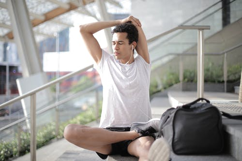 Young ethnic athlete in earbuds stretching body while sitting on stairs at entrance of contemporary building