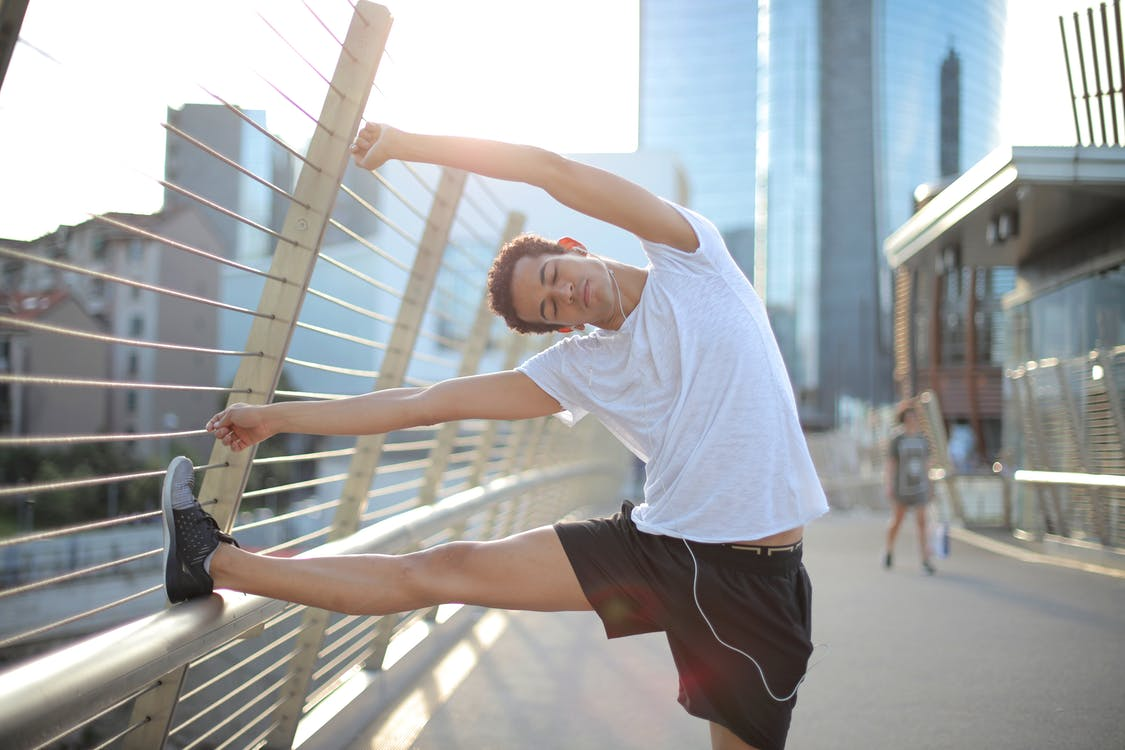 Calm focused  African American male athlete with eyes closed in earphones and sportswear leaning on metal fence and doing side bend exercise while listening to music and stretching body on street against blurred urban environment in sunny day