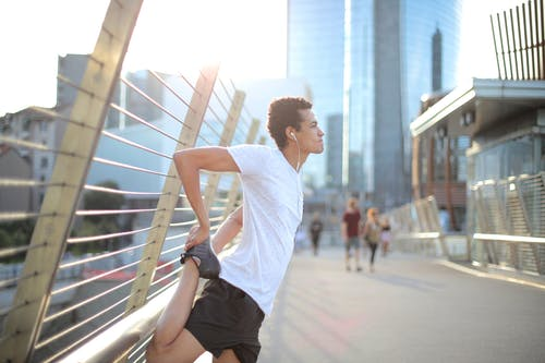 Focused millennial ethnic athlete in earphones listening to music and stretching body before running on street
