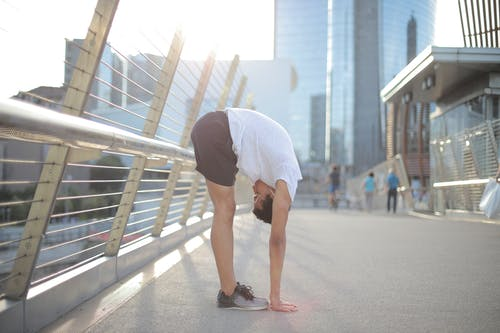 Flexible ethnic athlete doing standing forward bend exercise on street in city
